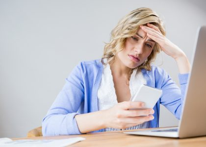 Stressed woman using her website finding out high cost of cheap website